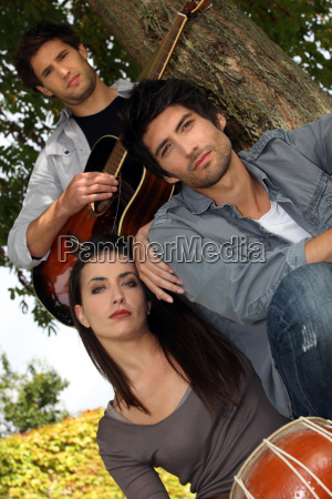 musicians sitting by a tree