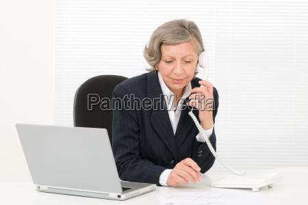 senior businesswoman serious sit behind office