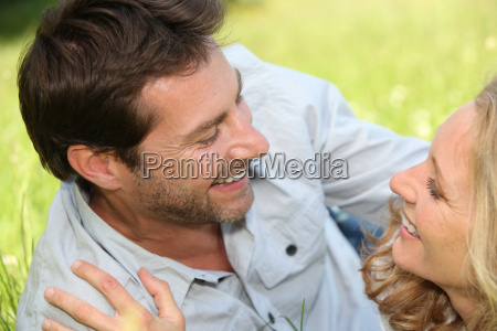 playful couple laid on grass