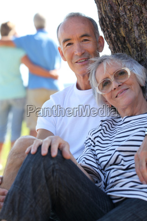 couple of pensioners posing seated against