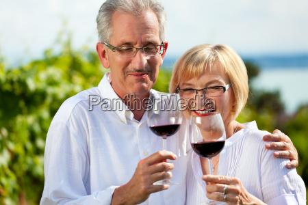 happy couple drinking wine at lake