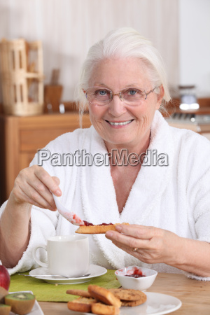 an old woman eating breakfast
