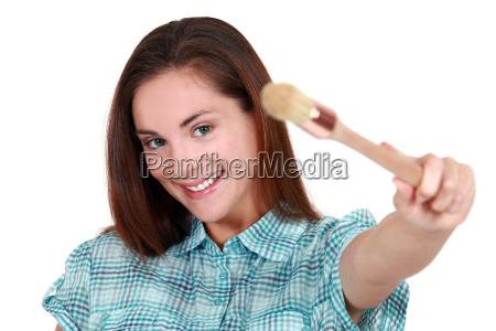 pretty young woman showing a brush