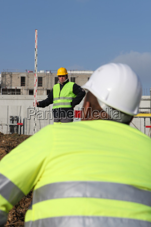 construction worker watching his colleague using