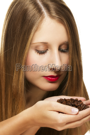 young beautiful woman smelling coffee beans