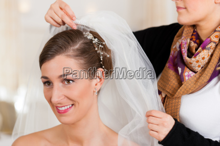 barber puts a bride hairstyle