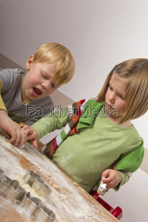 two children cutting out biscuits