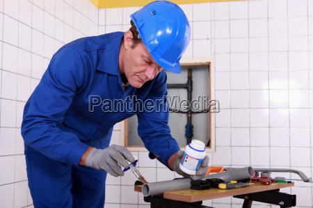 plumber applying glue to a grey