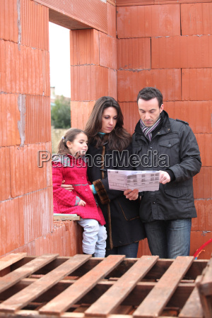 family walking around unfinished housing project