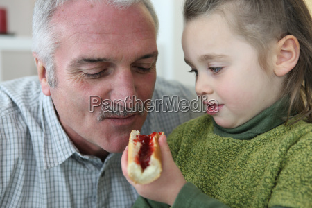 girl feeding her grandfather bread and