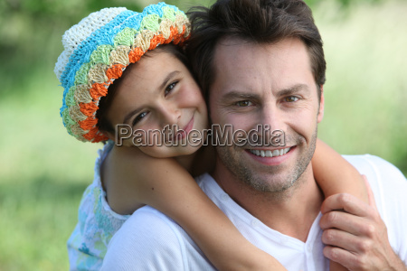 father carrying daughter on back