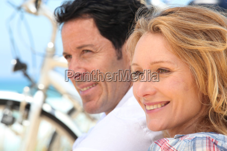headshot of couple with bikes by