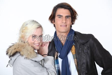 couple stood in studio wearing coats