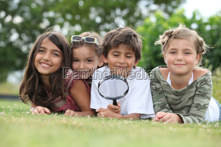 kids playing with magnifying glass in
