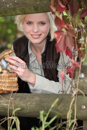 beautiful woman gathering mushrooms in the