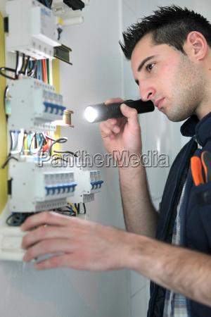 electrician examining fuse box