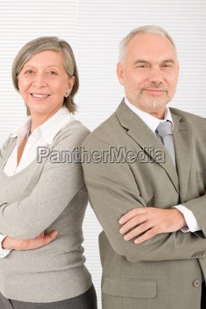 senior businesspeople smile cross arms portrait