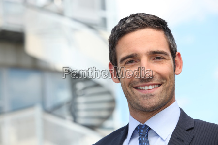 smiling business man standing outside office