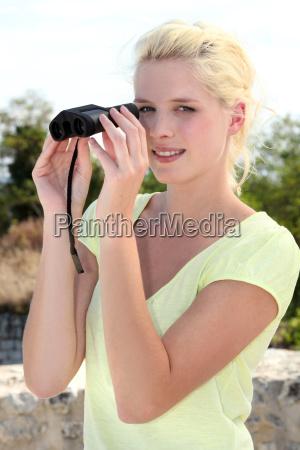 blond woman watching through binoculars