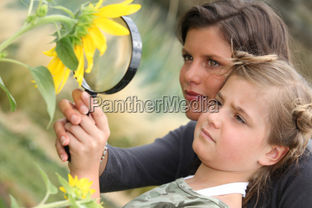 mother and daughter examining a sunflower