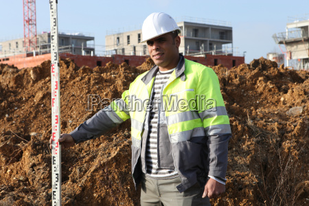 worker holding a yardstick