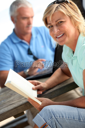 couple sat on park bench reading
