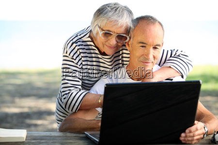 65 years old couple doing computer