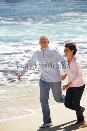 senior couple running along the beach
