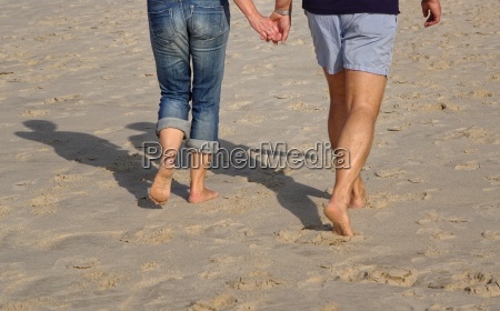 couple walking on the beach of