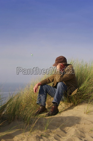 man sitting in the dunes on