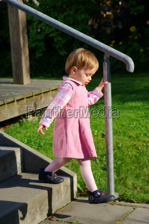 little girl goes down the stairs