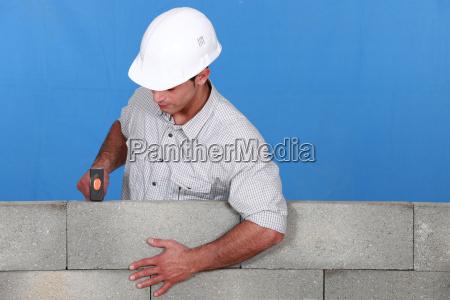 man straightening brick wall