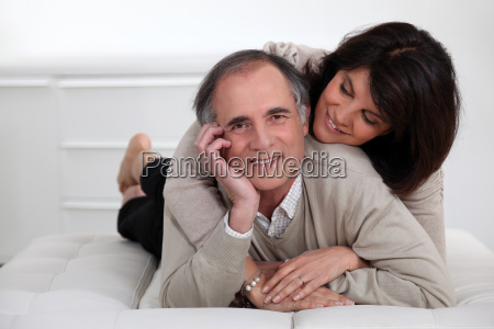 mature couple lying in bed showing