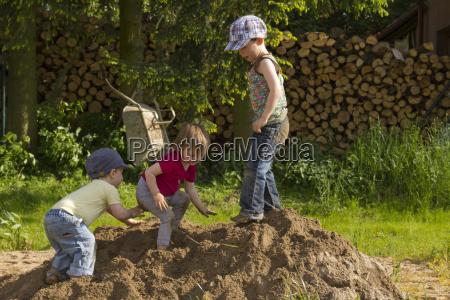 kinder spielen im sandhaufen