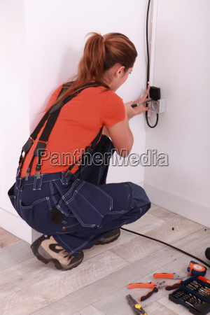 woman fixing electrical socket