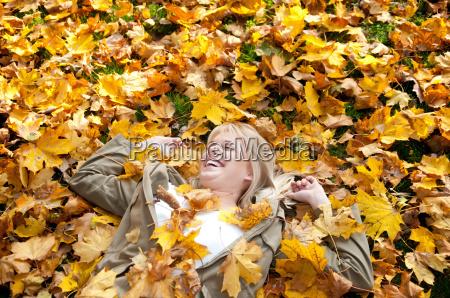 cheerful teenager in autumn foliage