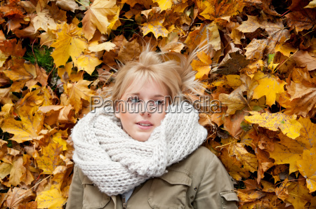 teenager in fall leaves