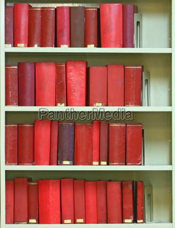 red old hardcover books on bookshelf