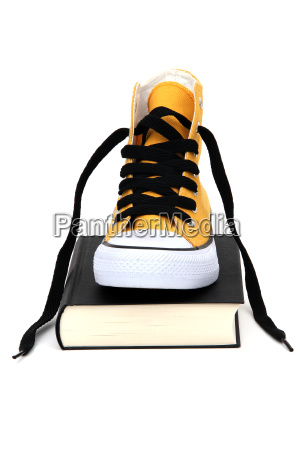 yellow sneaker on black book