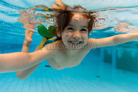 the girl smiles swimming under water