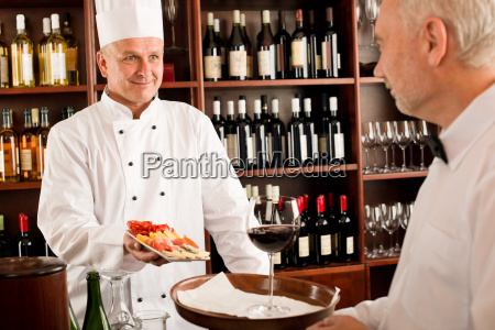 chef cook with tapas on tray