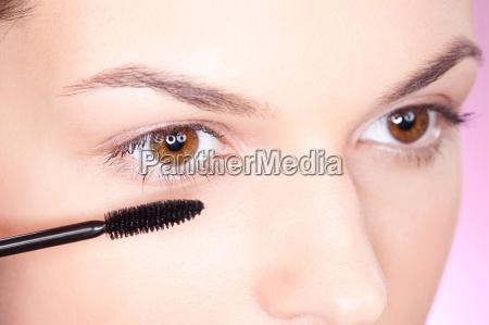pretty woman applying mascara on eye