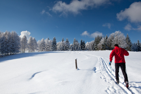 young man cross country skiing on