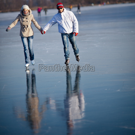 couple ice skating outdoors on a