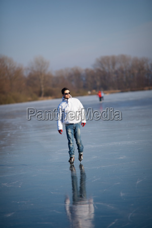 handsome young man ice skating outdoors