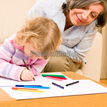 grandmother and granddaughter drawing at home