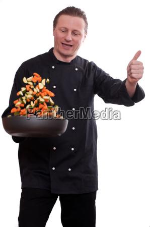 koch turns vegetables in a pan