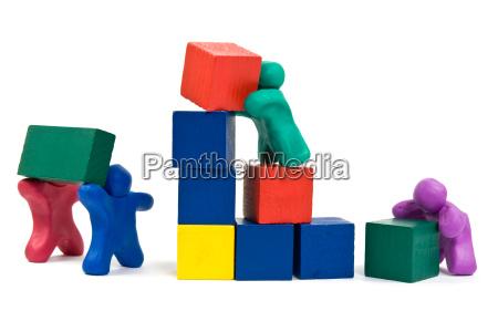 plasticine people building wooden blocks