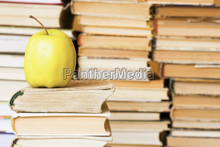 yellow apple on stack of books
