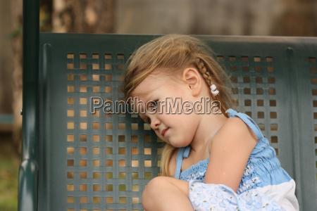 sad little child on a bench